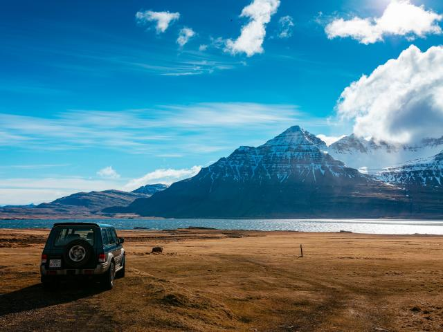 A car parked in front of a body of water and snow-capped mountain during an Iceland road trip