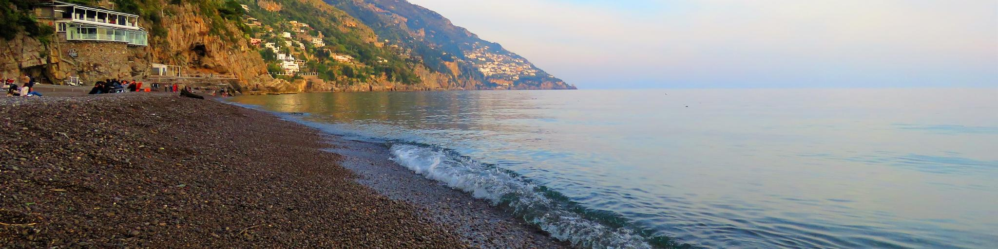 Waves lap against the pebble beach in Positano