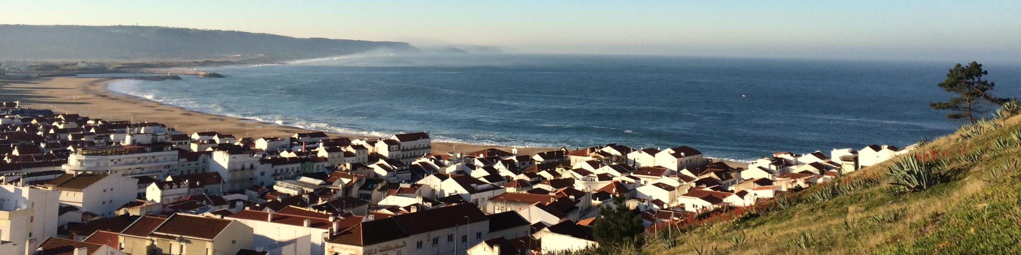 A view over the sandy coastline and red roofs of Nazare, Portugal