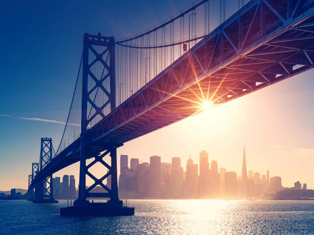 San Francisco skyline behind the Bay Bridge at sunset