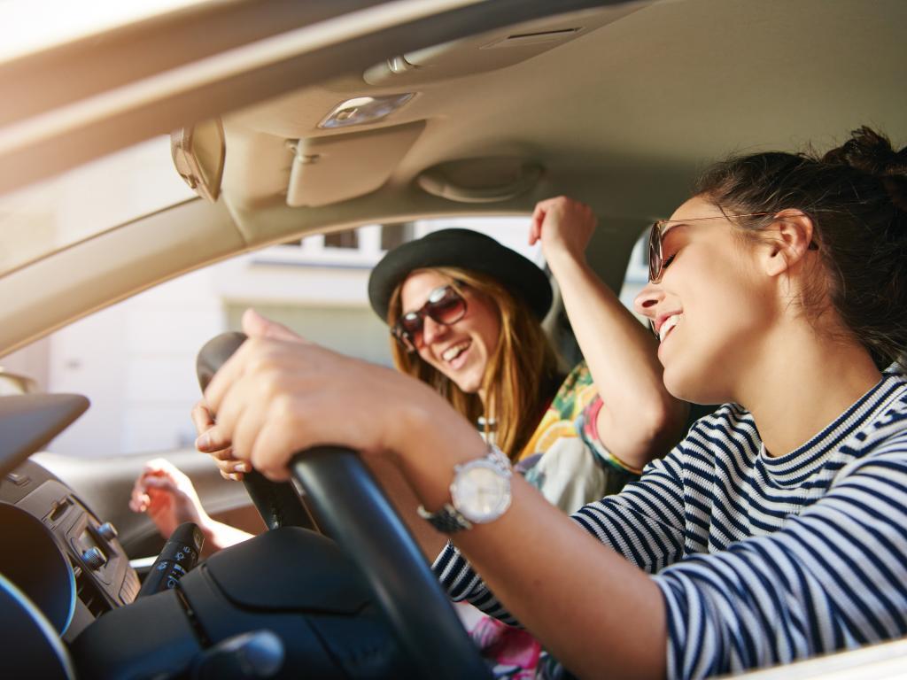 Two women enjoying playing Sing The Next Line game in their car.