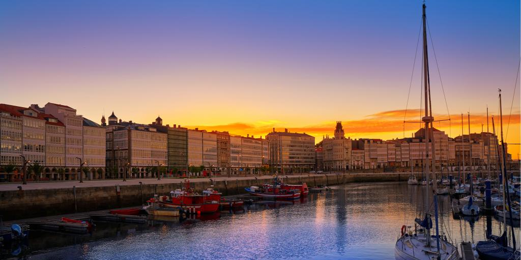 Sailboats float in the La Coruna marina at sunset