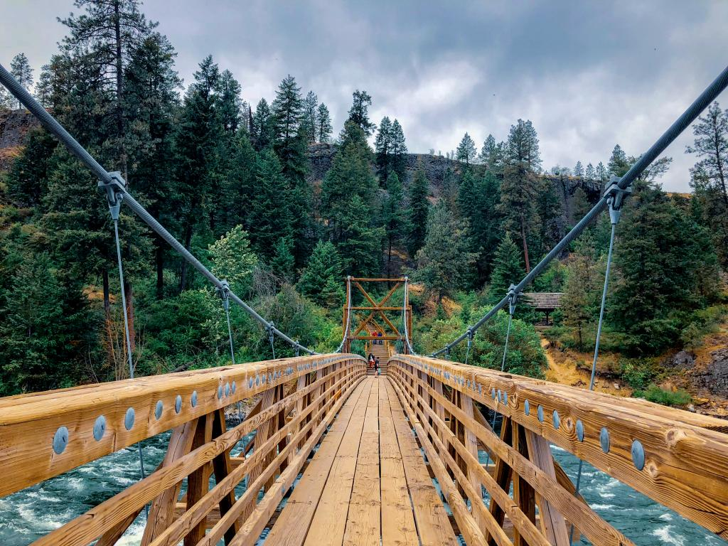 Two people on the other side of the wooden swinging bridge with tall green trees in their back and raging water in Riverside State Park, Spokane, Washington