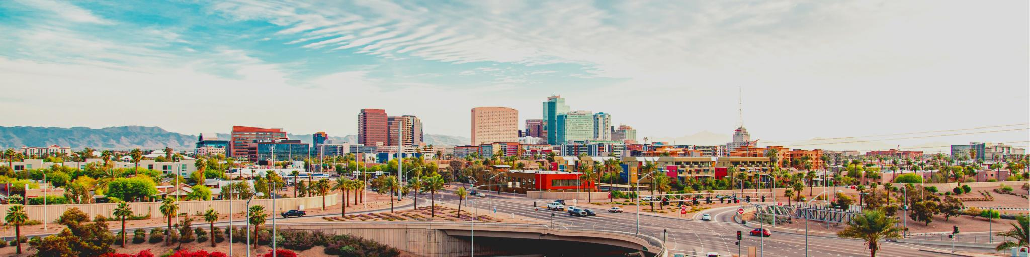 A scenic view of the cars driving along the intersecting highway with palm trees and bushes planted along the road with a picture of the skyscrapers of Phoenix in a fine day with a thin sheet of clouds covering the blue sky
