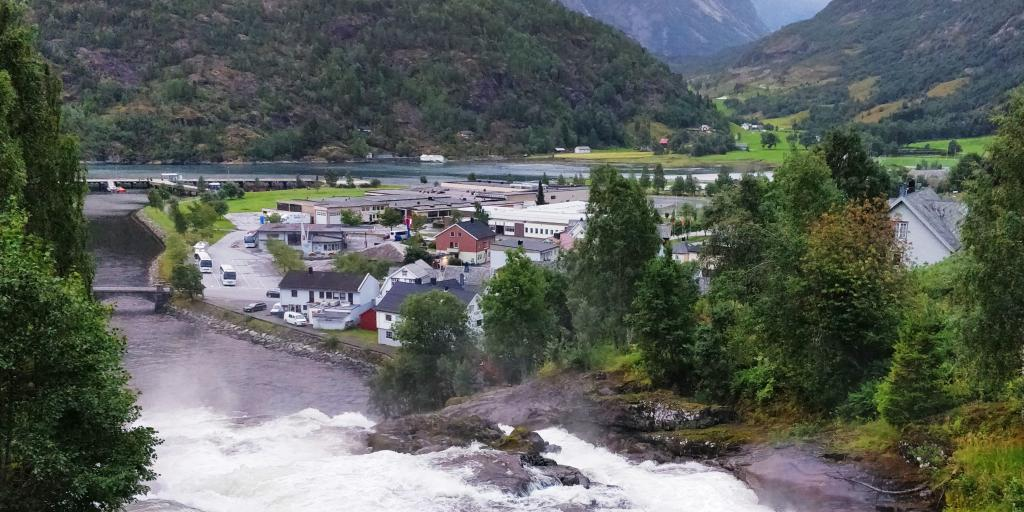 A waterfall gushes down from a mountain through the village of Hellesylt in Norway