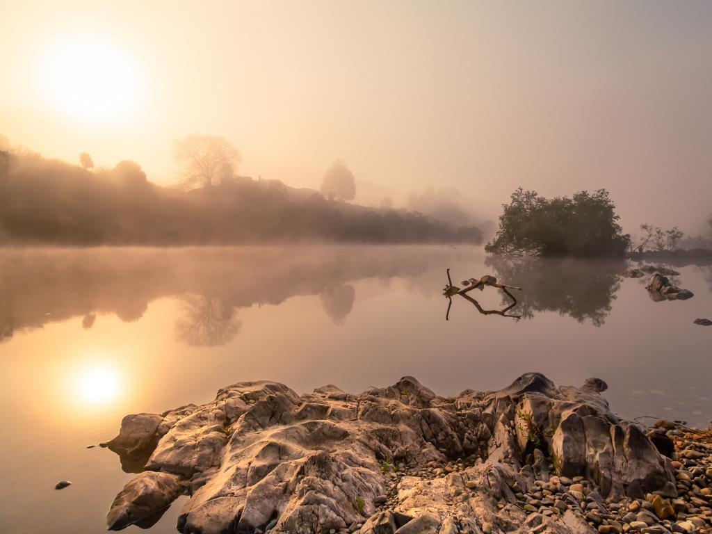 Sunrise cutting through the mist along the Nymboida River in New South Wales, Australia.