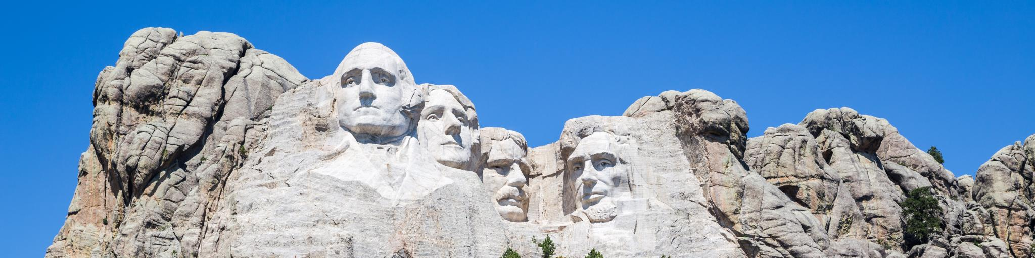 Shows the faces of past US presidents carved on granite as a massive sculpture on Mount Rushmore during a sunny day