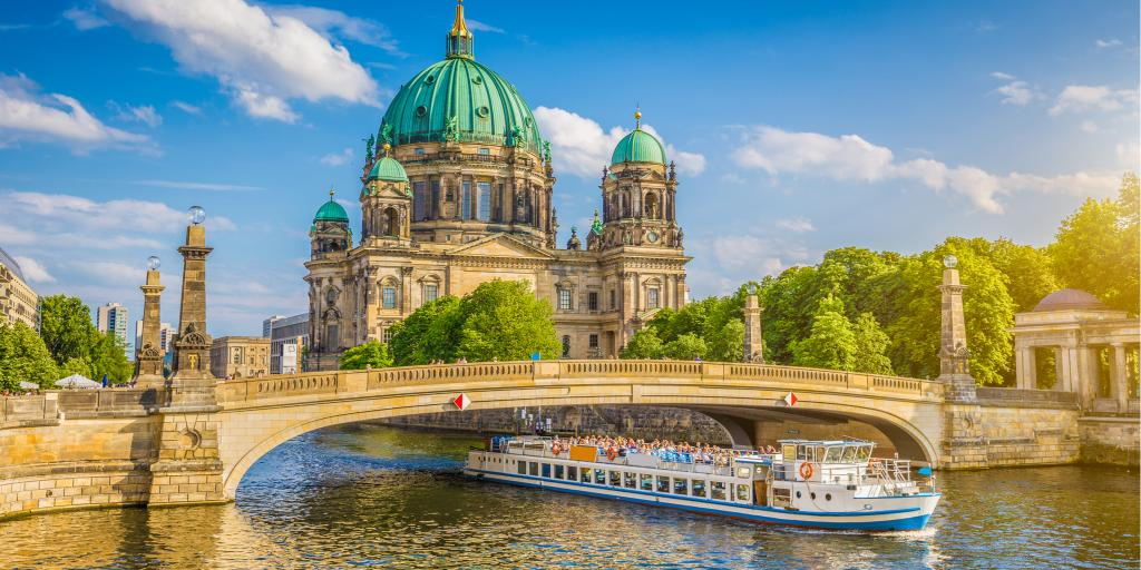 View of the Berlin Cathedral on Museumsinsel (Museum Island) with a boat going along the Spree river in Berlin