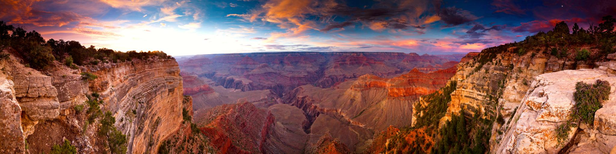 A fantastic view of the sunset reflecting the walls of Grand Canyon with a beautiful hue of pink and purple clouds in the blue sky