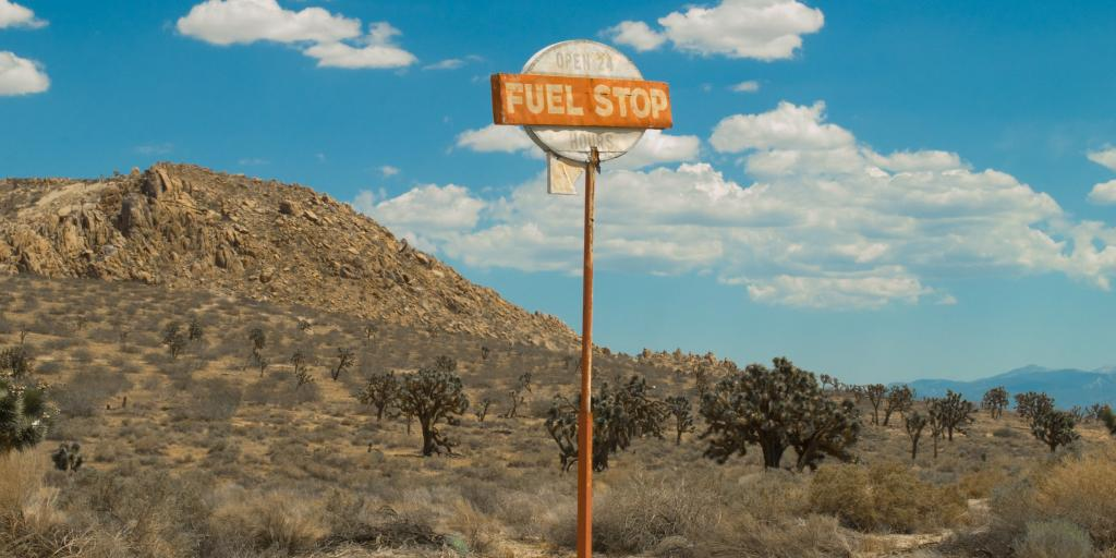 a vintage fuel stop sign in the middle of nowhere