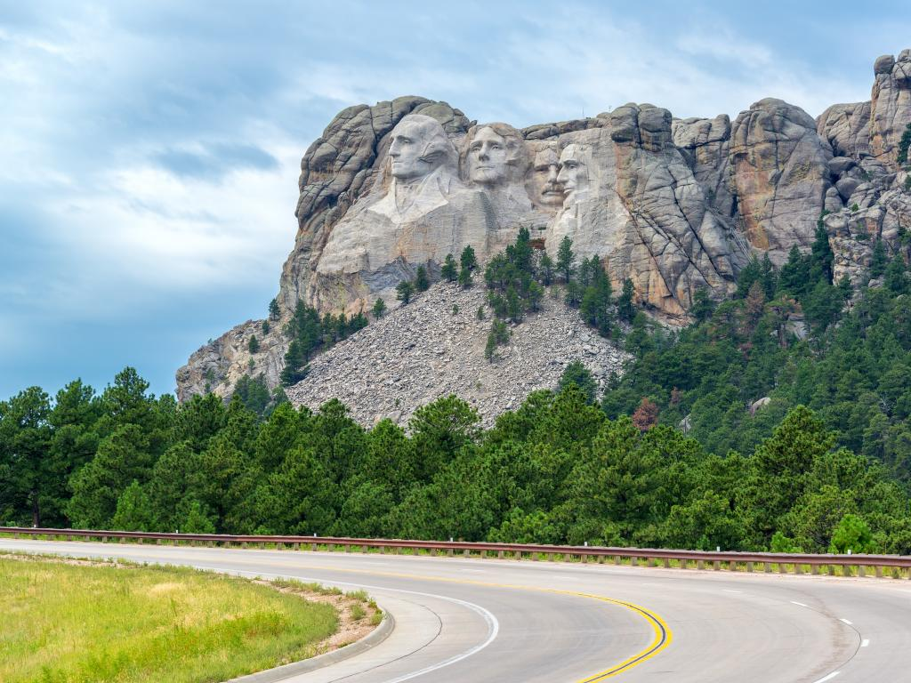 An empty curve road leading to Mount Rushmore National Monument in South Dakota and a view of the carved faces of the Four US Presidents in the mountain and green trees