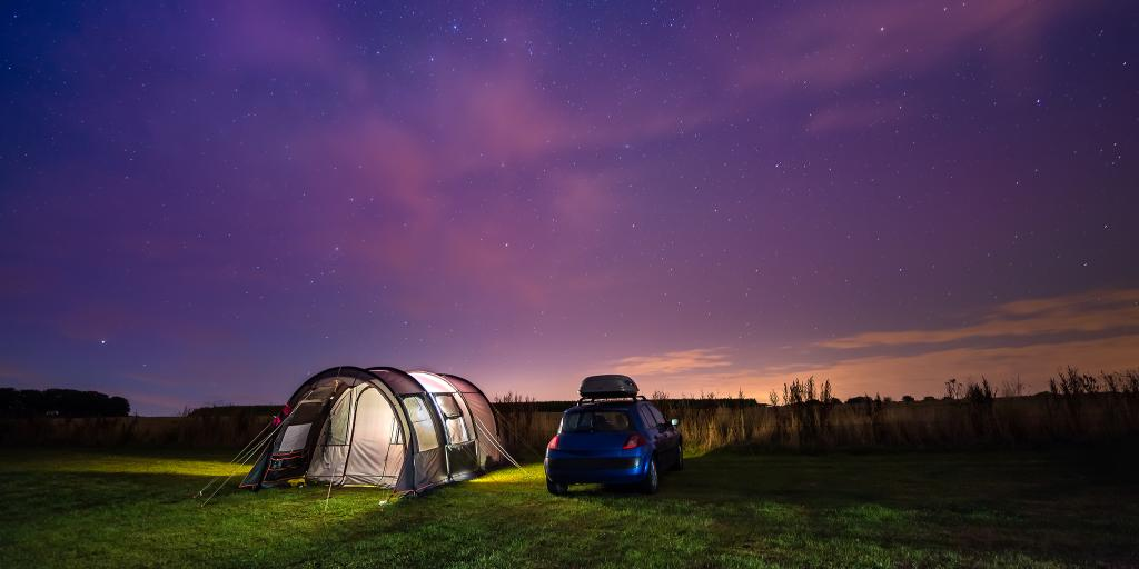 Tent and car under the night sky on a road trip