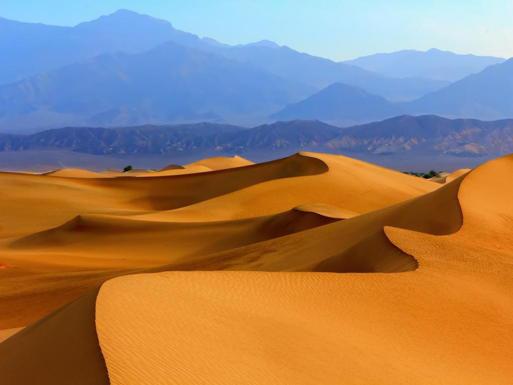 Sand dunes with mountains in the background in Death Valley National Park, California