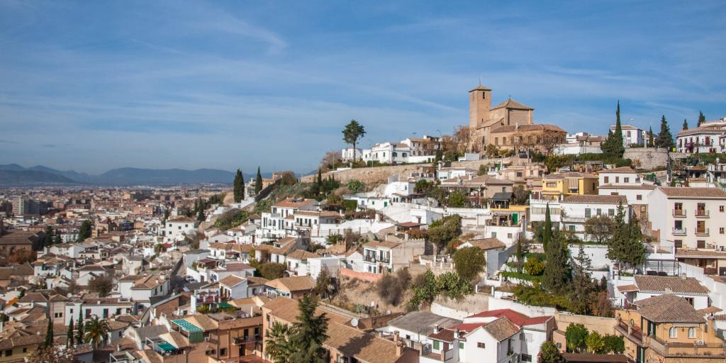 A view over the district of Albayzin, in Granada, Spain with lots of white and terracotta houses sprawling down the hillside