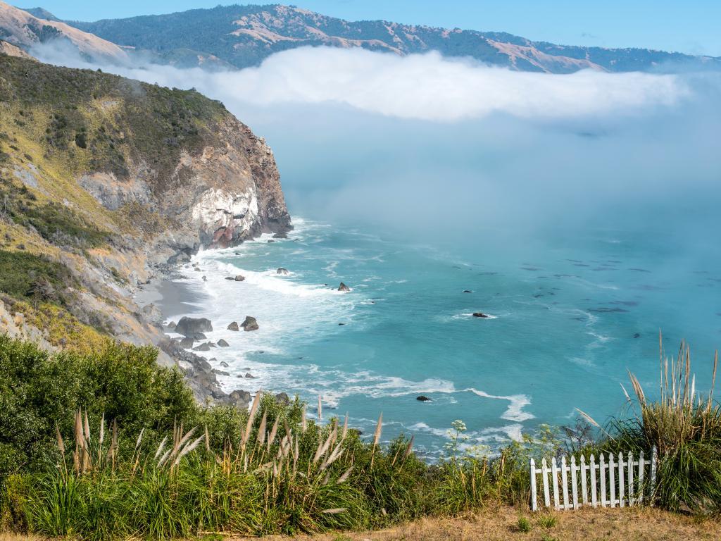 Waves crashing against the cliffs as the fog rolls in near San Luis Obispo, California