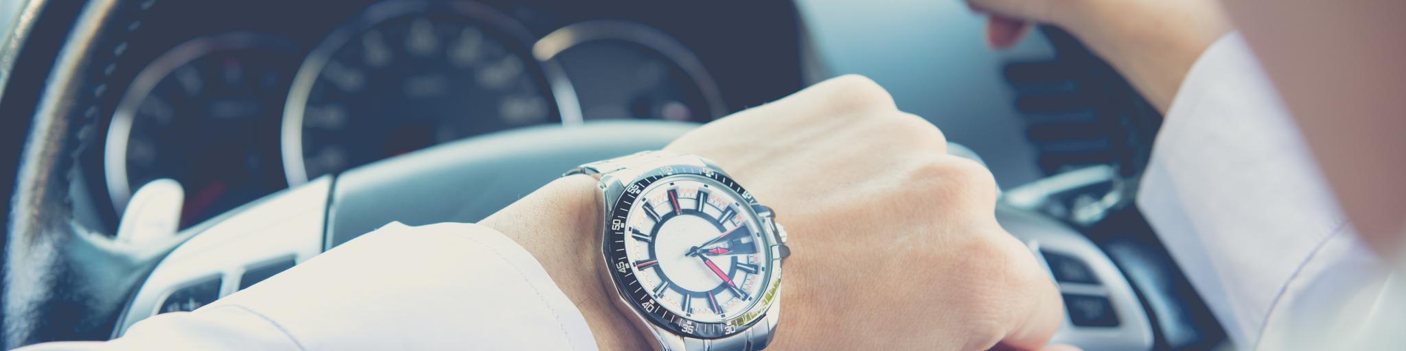 Man checking time behind steering wheel