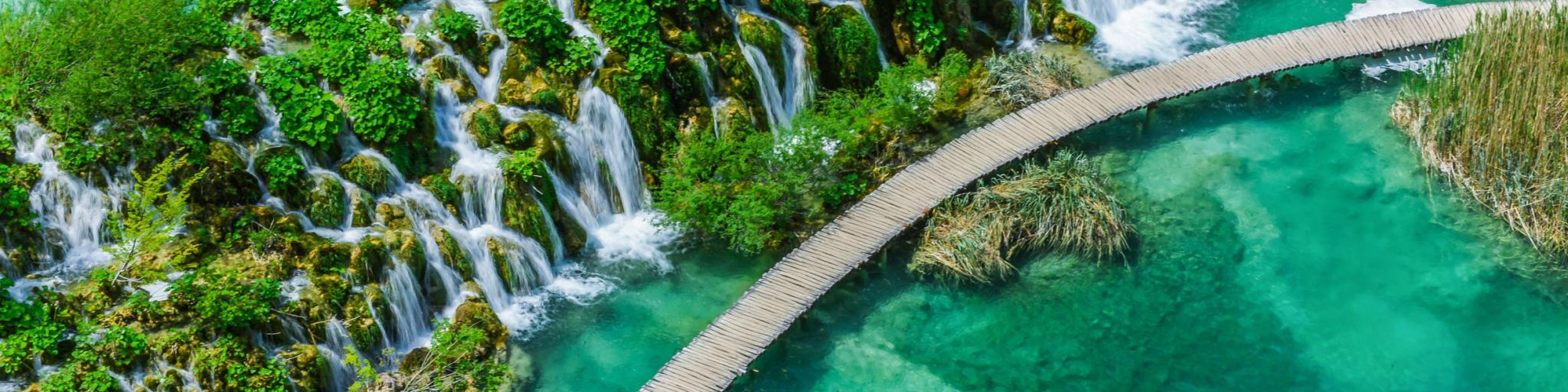 A footbridge snaking past waterfulls and above crystal blue waters at Plitvice Lakes National Park in Croatia