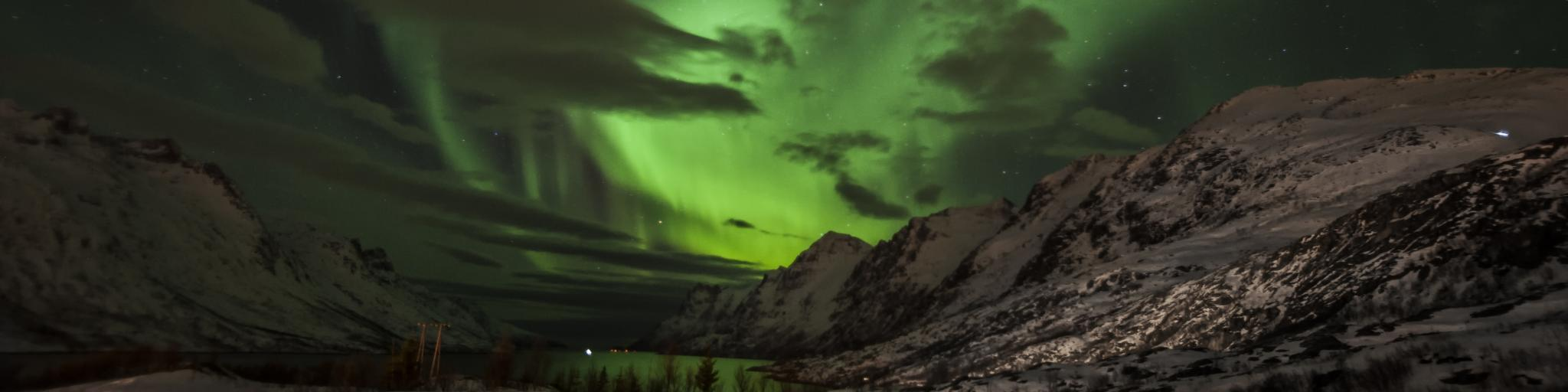 The Northern Lights dance above a mountain in Tromso, Norway