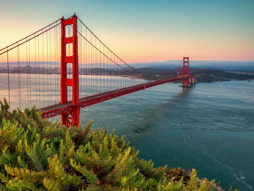 A scenic view of Golden Gate Bridge from Battery Spencer, Golden Gate National Recreation Area with a beautiful hue of orange and yellow sunrise in a clear blue sky.