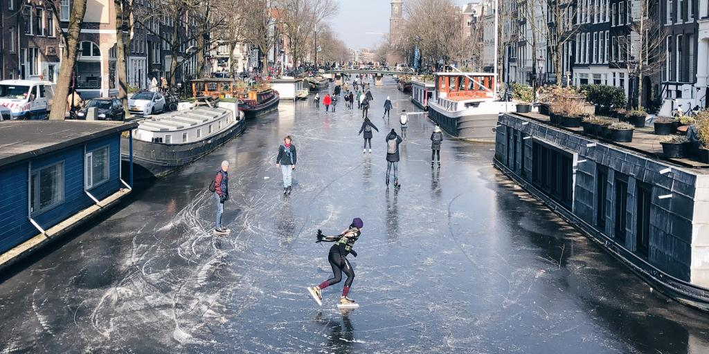 People ice skating on the frozen canal in Amsterdam