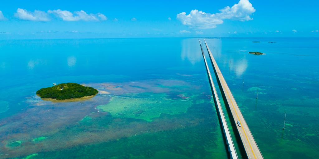 An aerial view of the straight 7 Seven Miles bridge on the Overseas Highway, Florida, with blue waters and reefs visible below the water