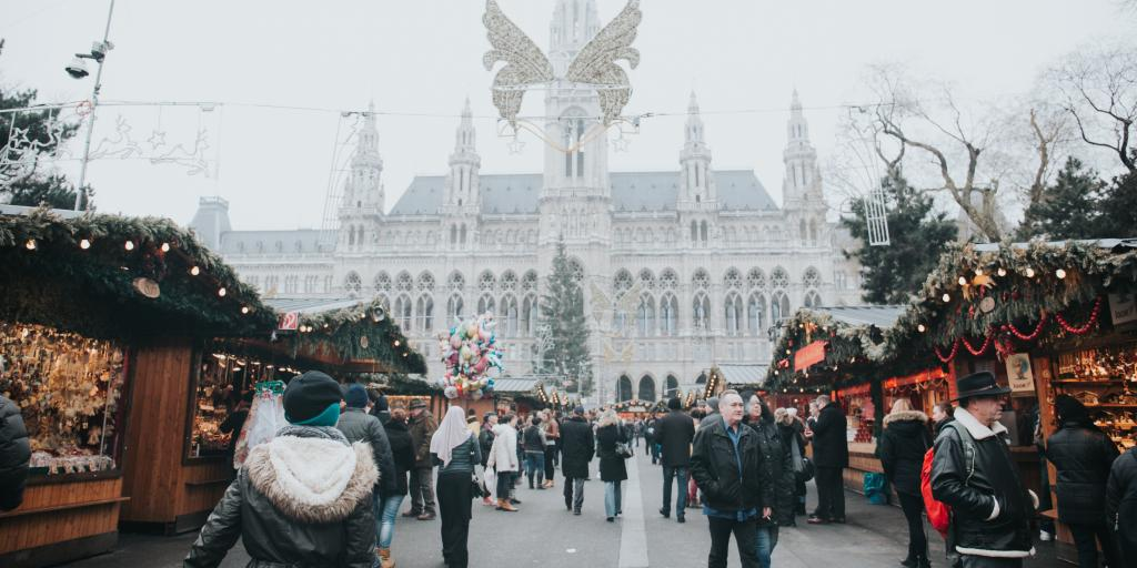 People walk through a Christmas market in front of Vienna City Hall