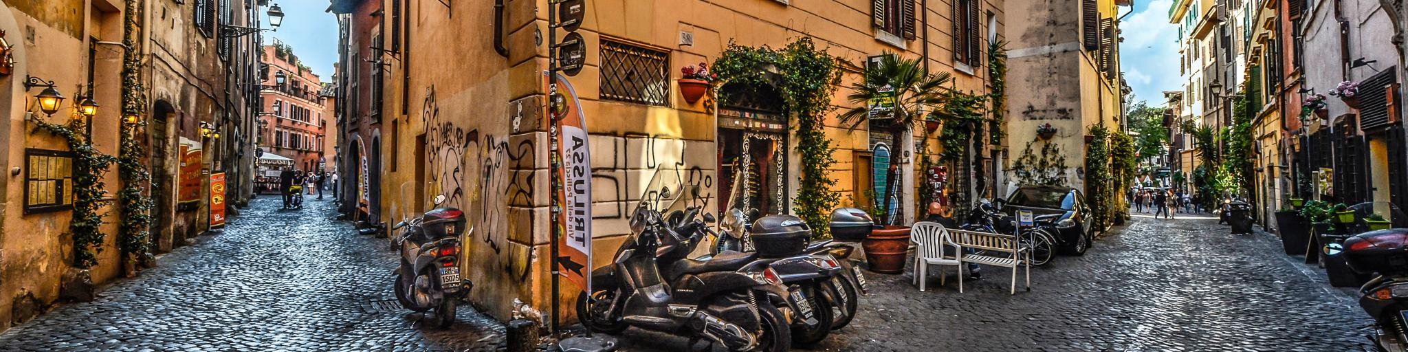 Two streets meeting in the area of Trastevere, Rome, with a sharp, yellow building in the centre and a row of scooters in the foreground