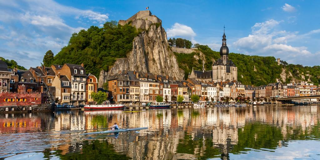 Houses and a church along the waterfront at Dinant, Belgium, with a person kayaking in the water