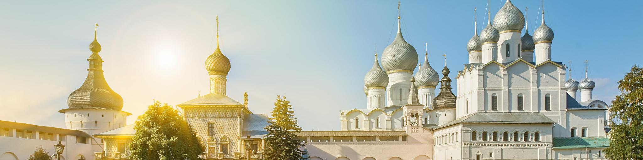 Sunlight streaming onto the white Assumption Cathedral and church of the Resurrection in Rostov Kremlin.