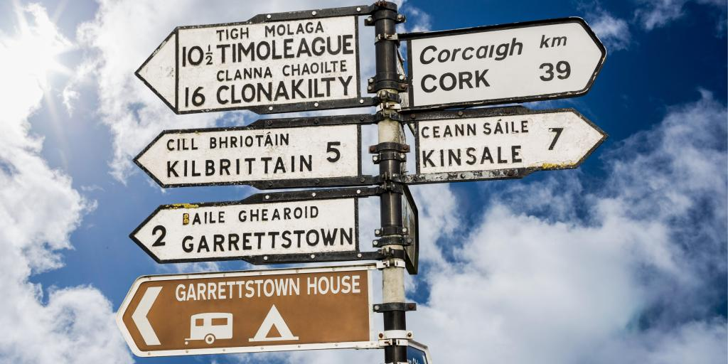 Irish road signs against a blue sky