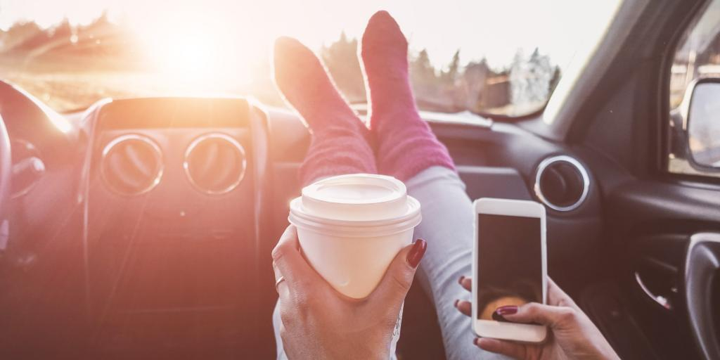 A person with their feet on a car dashboard holding a coffee in one hand and their phone in the other