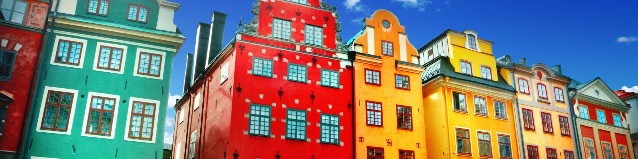Colourful townhouses in Stockholm, Sweden - from left to right: green, red, three yellow and another green