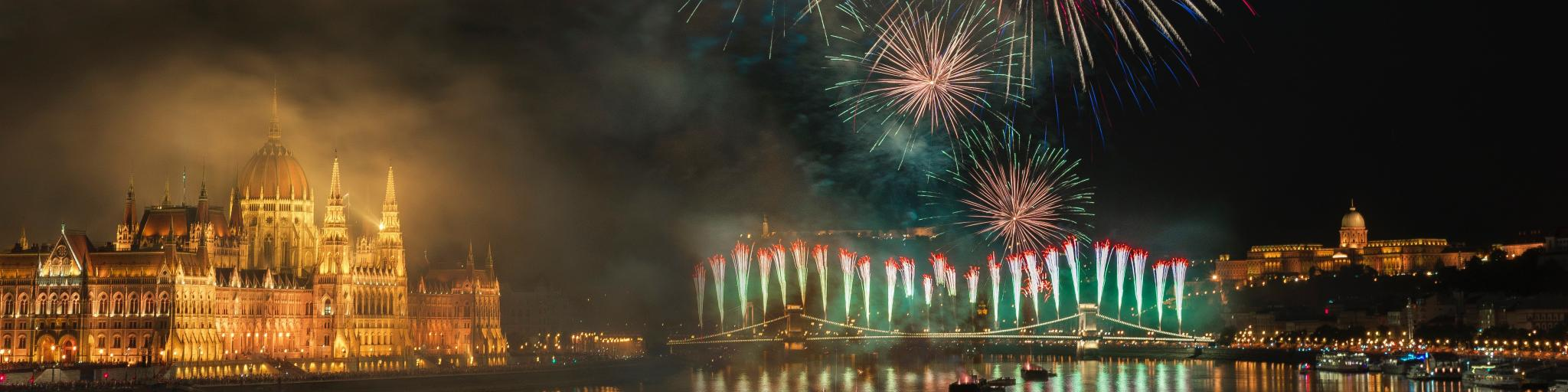 Fireworks exploding over the Danube in Budapest with the lit up Hungarian Parliament building to the side