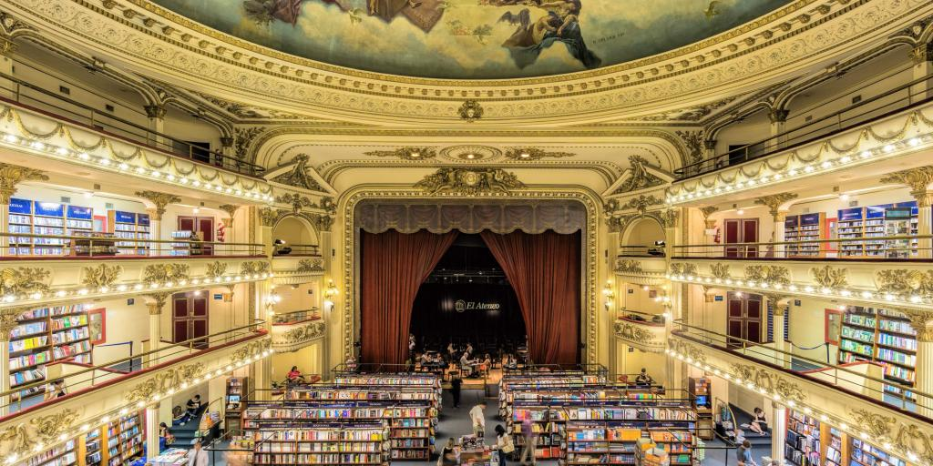 The inside of the El Ateneo Grand Splendid, Buenos Aires, Argentina, with a grand ceiling fresco, ornate gold surroundings and rows of books visible