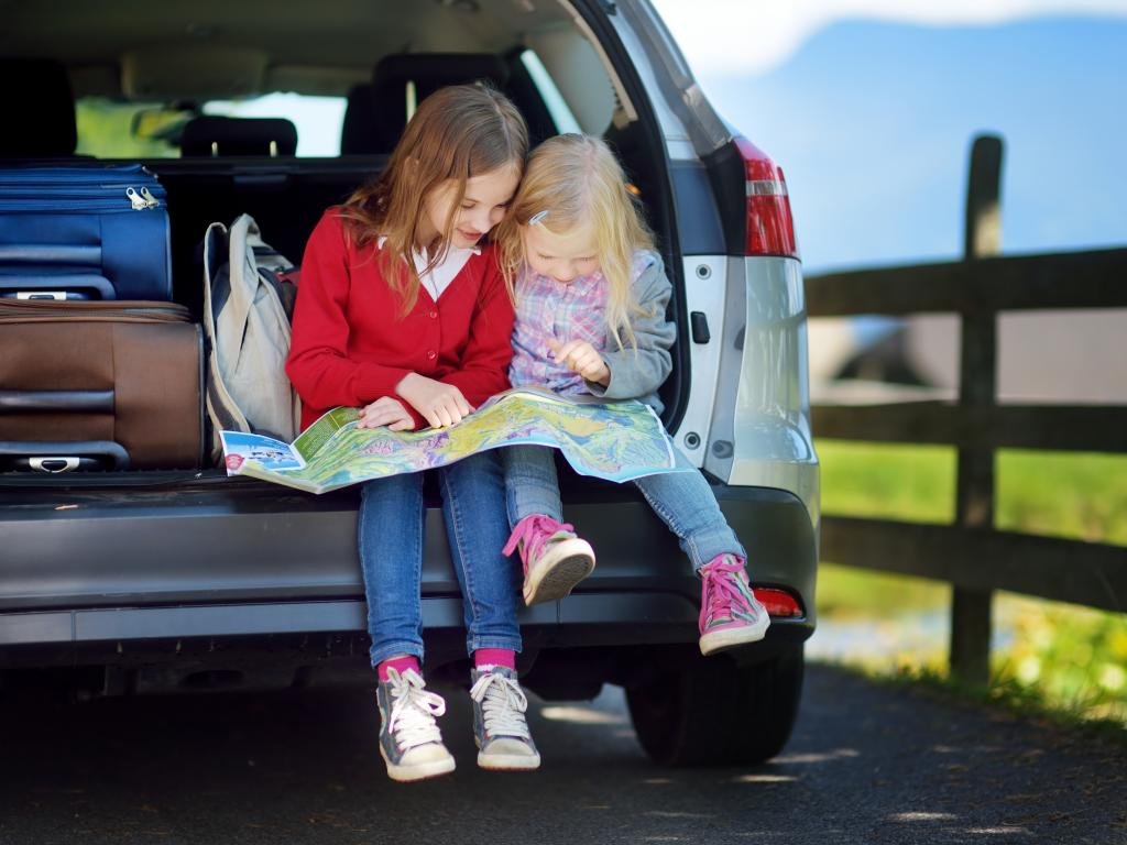 Kids looking at a map to find secret places along the road trip route.