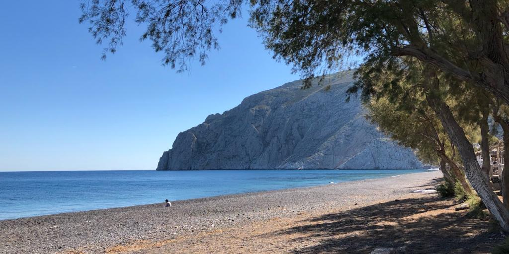 A tree overhangs the empty Kamari Beach on Santorini, with dramatic cliffs in the background