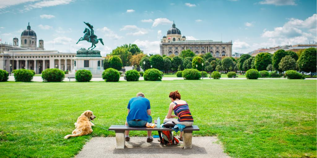 Two friends sitting on the bench with beautiful view to Vienna panorama with a dog