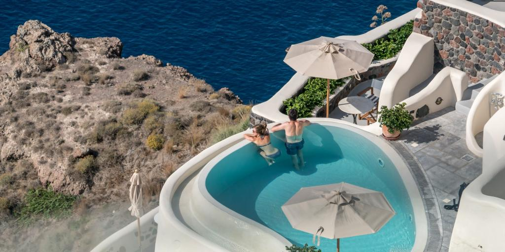 A couple look out at the views from their private terrace pool in Santorini, Greece