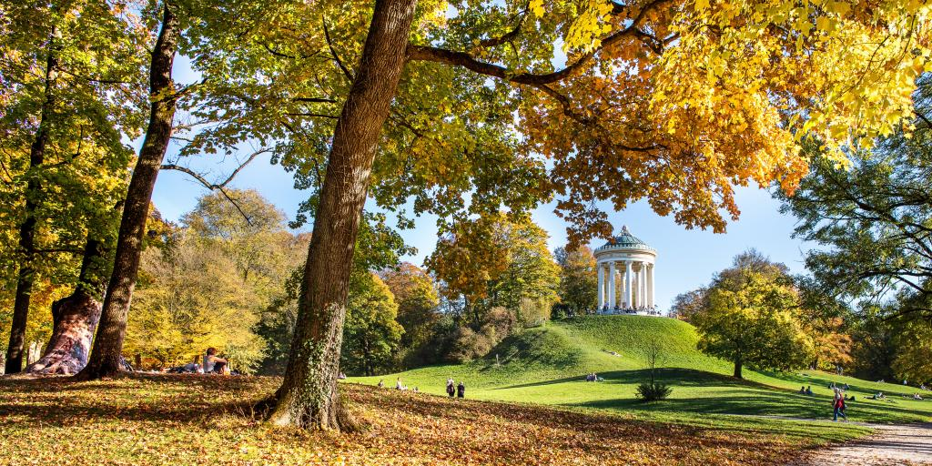 The English Garden Munich on an Autumn day, with the Greek Temple shown sitting on a grassy hill and lots of colourful leaves and trees