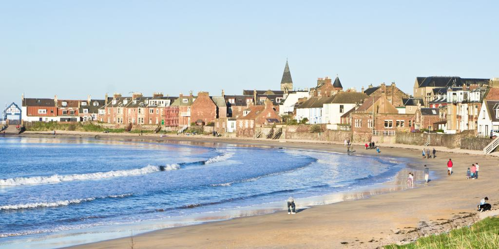 People walk along the beach on a sunny day in North Berwick, Scotland