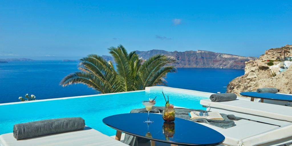 Two hotel loungers by a pool over looking the caldera in Santorini
