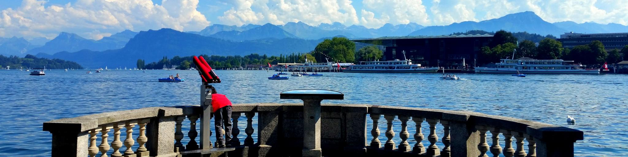 A boy looks over a balcony into Lake Lucerne, with boats and the Swiss Alps in the background