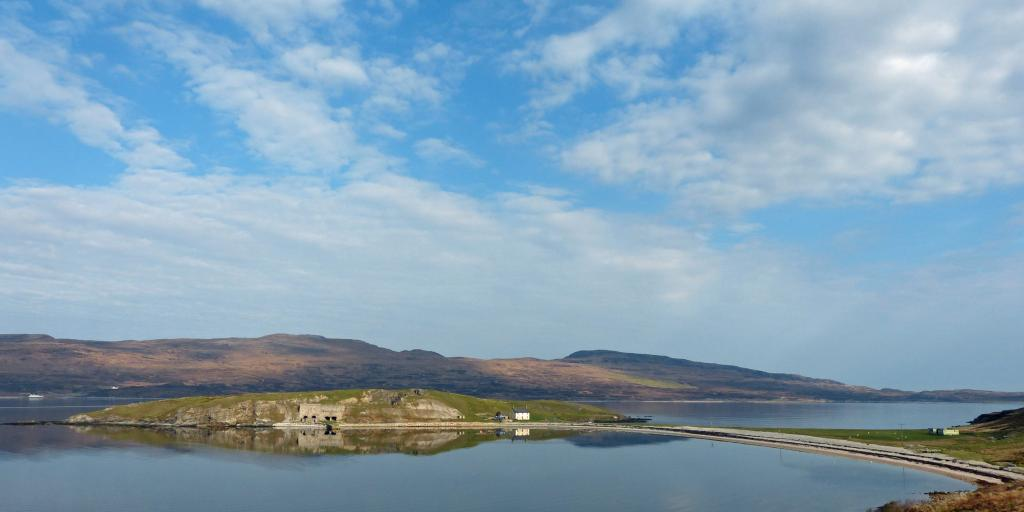 Square lime kilns on a promontory in Loch Eriboll, with the mountains in the background and blue skies