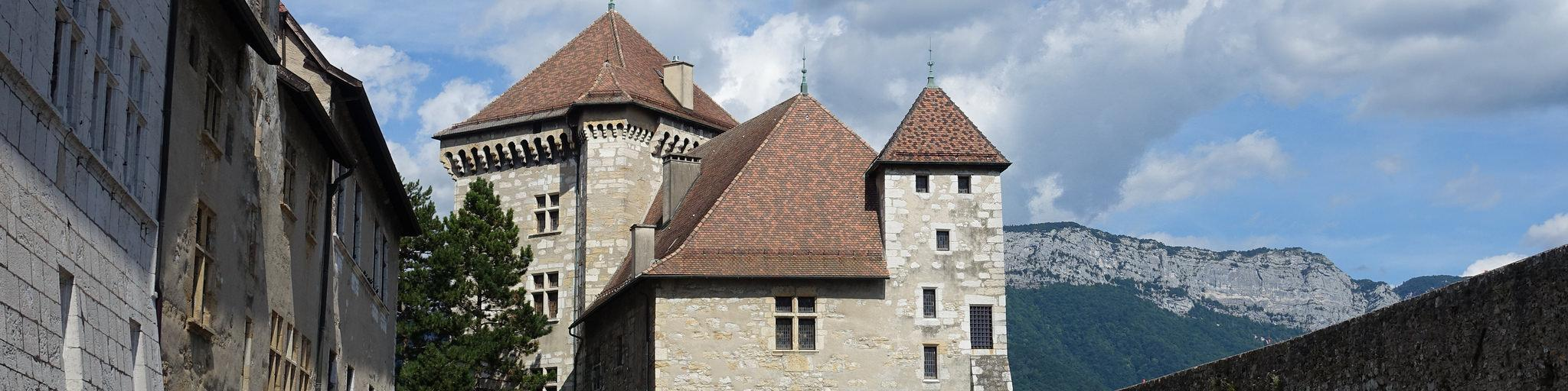 The courtyard of the Château d'Annecy with the square buildings of the castle in the foreground and mountains in the background