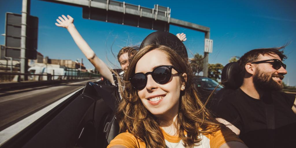 Happy group of friends taking selfie when road trip in convertible car on a sunny day
