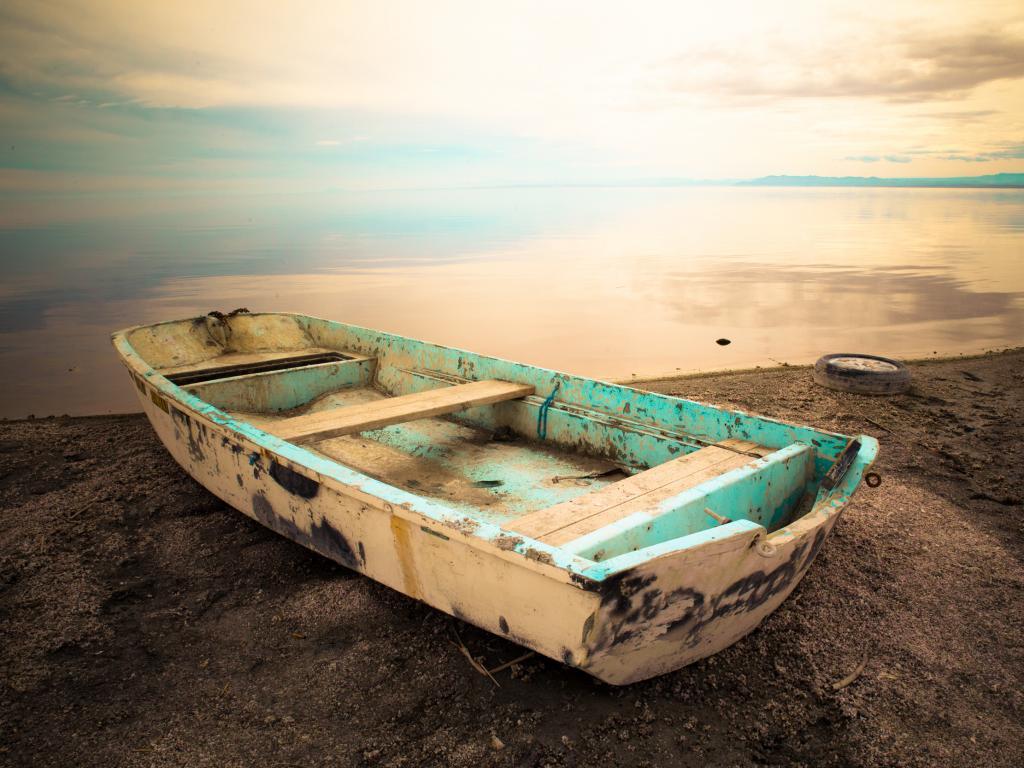 An old boat sitting on the edge of Salton Sea, California