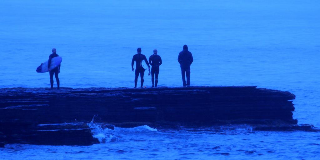Three wetsuit-clad surfers and a man in a hoody stood on a rock and looking out to sea in Thurso, Scotland