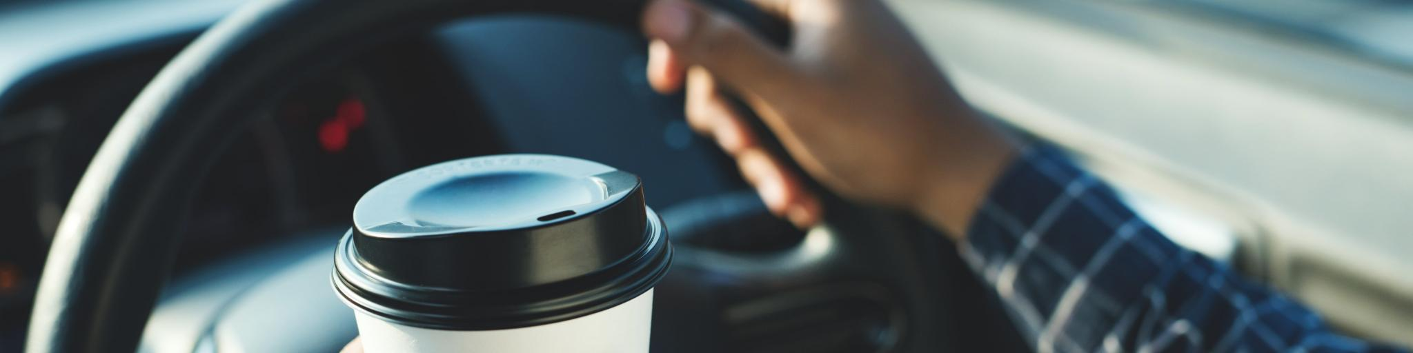 A person holding a coffee in front of a steering wheel