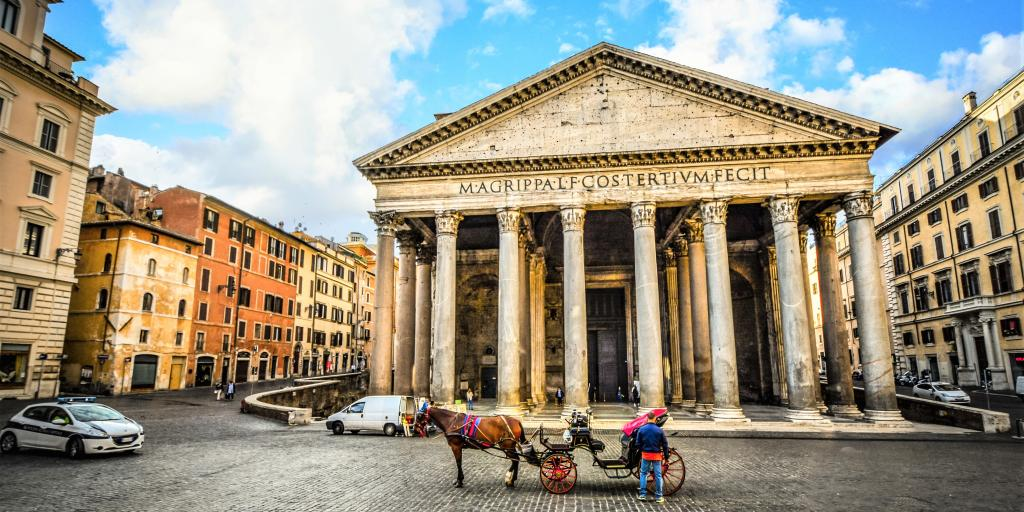 A view of the column fronted Pantheon, Rome, with blue skies and a horse and cart in the foreground
