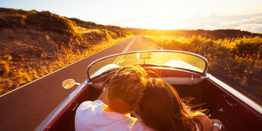 A couple driving down a road at sunset with his arm around her shoulder